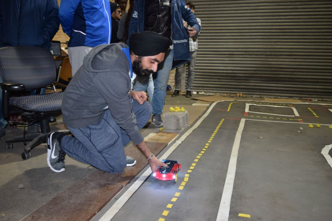 Student sets vehicle on the course during the AV class at the UIC College of Engineering.