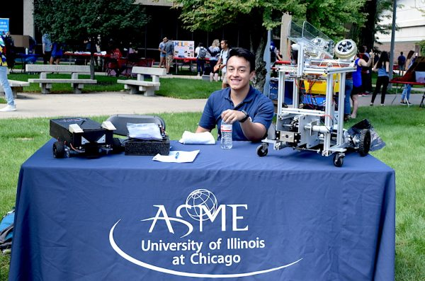 ASME student sitting at display table