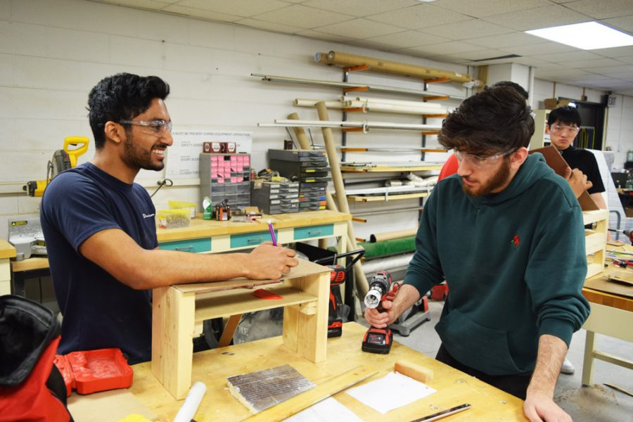 two students building a wooden prototype