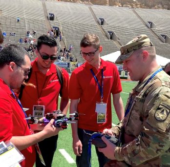 Engineering students present their drone to an Army judge.