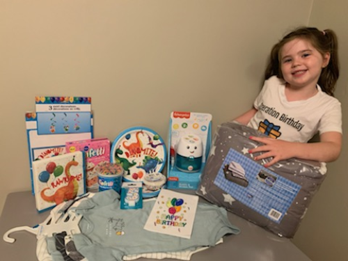 Shelby-Ann poses with the supplies from a birthday kit.